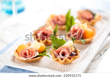Tarts with meat, basil, melon balls and figs.  - stock photo