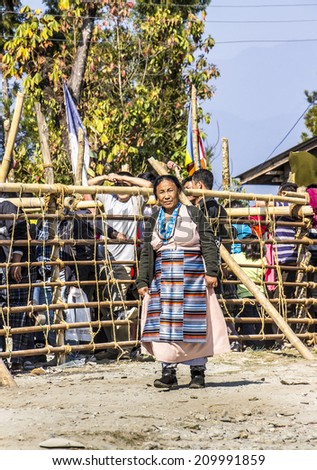 TASHIDING, INDIA - MARCH 16, 2014: A tibetan woman in traditional costume at the bumchu festival, Tashiding, Sikkim. In the background buddhist believers are queuing to get into the temple. - stock photo