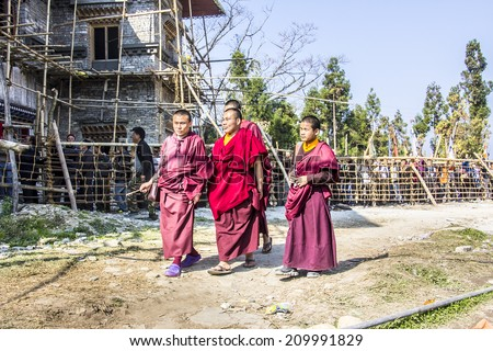 TASHIDING, INDIA - MARCH 16, 2014: Four monchs at the bumchu festival, Tashiding, Sikkim. In the background buddhist believers are queuing to get into the temple. - stock photo