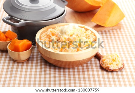 Taste rice porridge with pumpkin in bowl on tablecloth background
