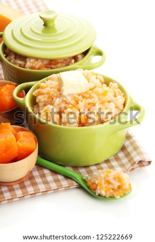 Taste rice porridge with pumpkin in saucepans, isolated on white - stock photo