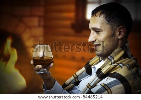 Taster. Young adult Man in tartan plaid holding in hand a glass of classy extra old brandy or cognac. He is inside home room siting about fireplace - stock photo