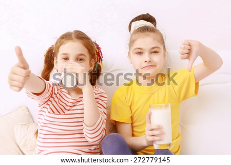 Tastes are different. Two cute kids drinking milk and  judging it - stock photo