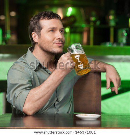 Tasting a good beer. Portrait of thoughtful men drinking beer at the bar - stock photo