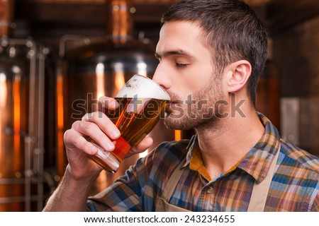 Tasting fresh brewed beer. Handsome young male brewer in apron tasting fresh beer and keeping eyes closed while standing in front of metal containers - stock photo