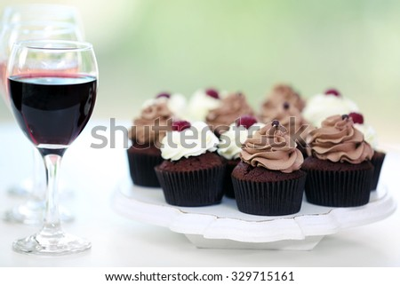 Tasting of wine and chocolate cupcakes, close up - stock photo
