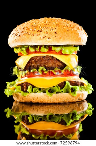 Tasty and appetizing hamburger on a dark background