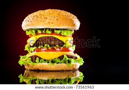 Tasty and appetizing hamburger on a darkly red background - stock photo