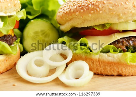 Tasty and appetizing hamburger on wooden  plate - stock photo