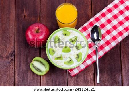 Tasty and delicious breakfast of oatmeal and fruit. Fresh orange juice, oatmeal with yogurt, kiwi and apple. Breakfast for the student or the student. Healthy lifestyle. - stock photo
