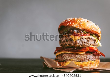 tasty and delicious juicy burger with beef and bacon on a grill. dark wooden background