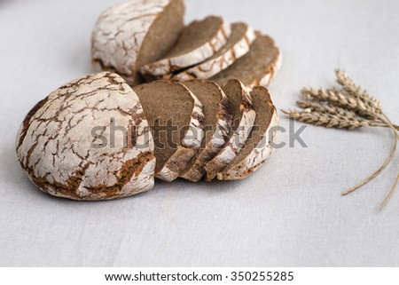 Tasty and delicious sliced loaf of bread on a board. Bread is on a background of linen fabric. - stock photo