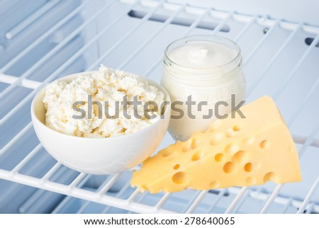 tasty and healthy dairy products on the shelf in the refrigerator: sour cream in the bank, cottage cheese in  bowl and slab of cheese  - stock photo