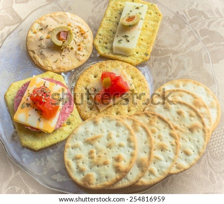 Tasty Appetizer. Water crackers with olives, cheeses, tomatoes and meats. - stock photo