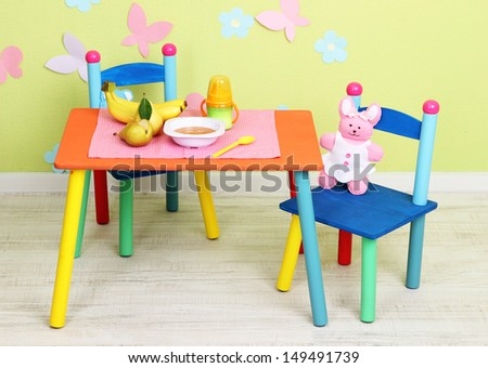 Tasty baby fruit puree and baby bottle on table in room - stock photo
