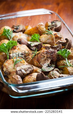 Tasty baked chicken legs with potatoes, mushrooms and herbs - stock photo