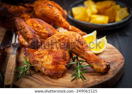 Tasty baked chicken with herbs and lemon - stock photo