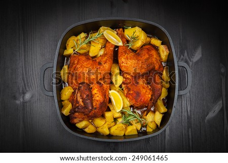 Tasty baked chicken with potatoes and herbs - stock photo