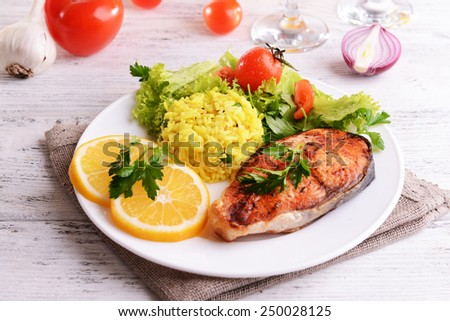Tasty baked fish with rice on plate on table close-up - stock photo