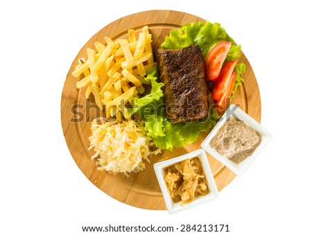 Tasty baked meat, tomatoes, french fries and sauces on a wooden board  - stock photo