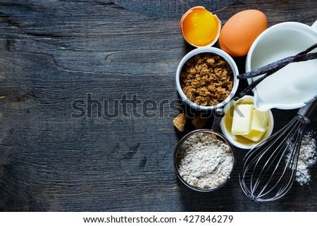 Tasty baking concept background with ingredients for making cake over vintage wooden board.Top view composing with space for text. Flat lay. Dark rustic style. - stock photo