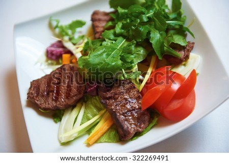 tasty bbq meat food, juicy beef steak with grilled cheese and salad in restaurant - stock photo