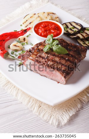 Tasty beef steak and grilled vegetables close-up on a plate. vertical  - stock photo