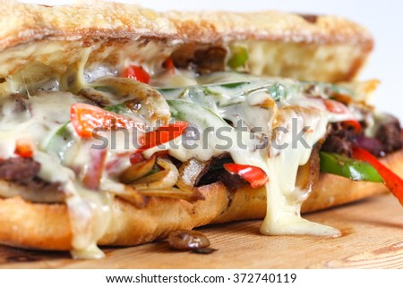 Tasty beef steak sandwich with onions, mushroom and melted provolone cheese in a ciabatta - stock photo