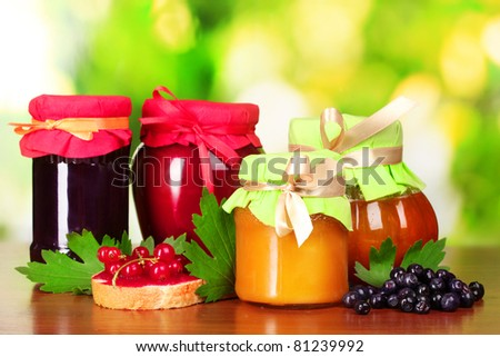 tasty berry and fruit jam and berry on a green background Listen berry and fruit jam and fruit Listen tasty berry and fruit jam and berry - stock photo