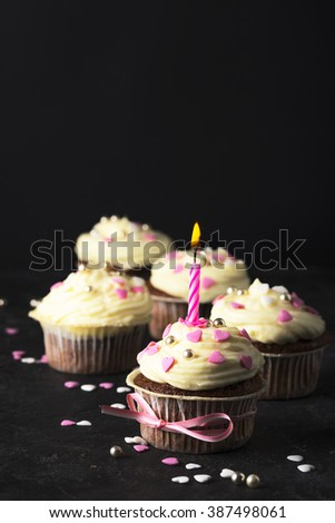 Tasty birthday cupcake with candle, on black background. Toned for art effect. - stock photo