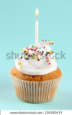 tasty birthday cupcake with candle, on blue background