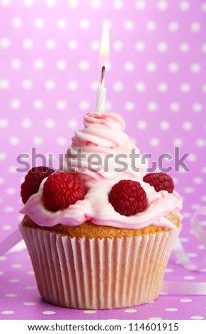 tasty birthday cupcake with candle, on violet background - stock photo
