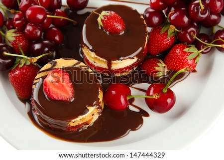 Tasty biscuit cakes with chocolate and berries on plate, close up - stock photo