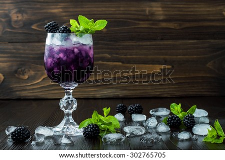 Tasty blackberry cocktail in wine glass with mint and ice on dark wooden table. Summer berry lemonade. Copy space background  - stock photo