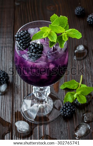 Tasty blackberry cocktail in wine glass with mint and ice on dark wooden table. Summer berry lemonade - stock photo