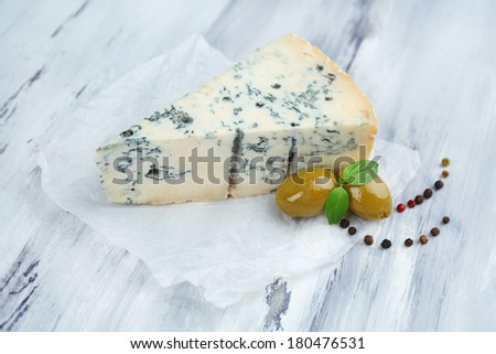 Tasty blue cheese on old wooden table - stock photo