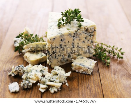 Tasty blue cheese with thyme, on wooden table - stock photo