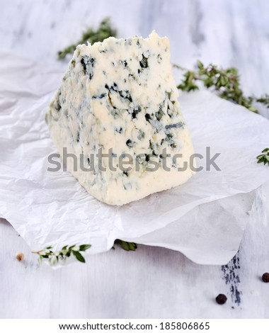 Tasty blue cheese with thyme on wooden table - stock photo
