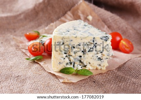 Tasty blue cheese with tomatoes and basil, on burlap background - stock photo
