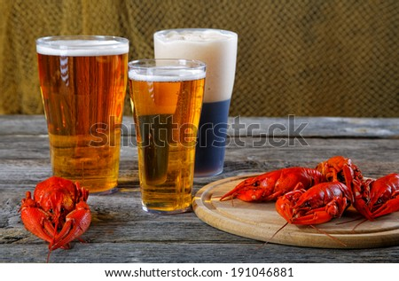Tasty boiled crayfishes and beer on old table - stock photo