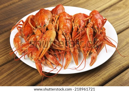 Tasty boiled crayfishes on a wooden table - stock photo