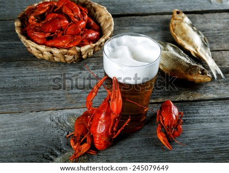 Tasty boiled crayfishes vyaleny fish and beer on old table - stock photo