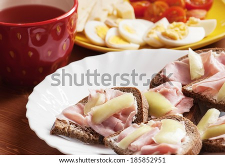 Tasty bread with ham, paprika, eggs, tomatoes and fruit tea.