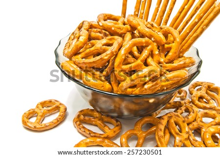 tasty breadsticks and salted pretzels on white closeup - stock photo