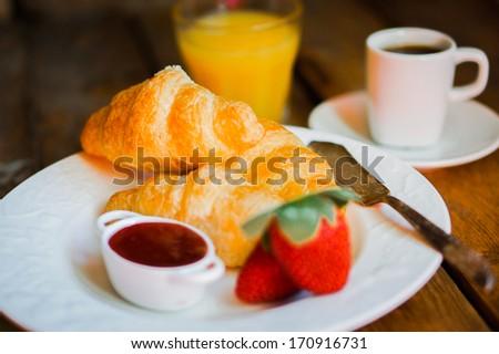 Tasty breakfast:coffee with croissants,orange juice,strawberries - stock photo