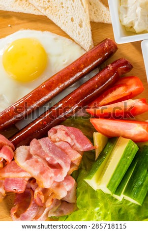 Tasty breakfast - toasts, fried egg, sausages, meat and vegetables on wooden board  - stock photo