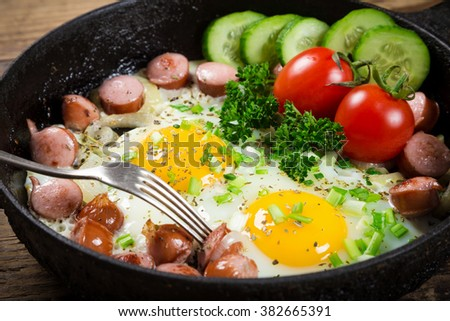 Tasty breakfast - two fried eggs with sausages in pan - stock photo
