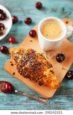 Tasty breakfast with fresh croissant, coffee and cherries on a wooden table, selective focus on croissant - stock photo