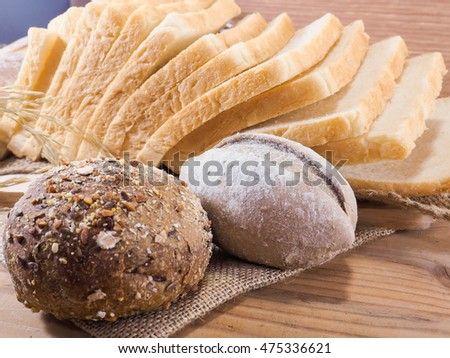 Tasty buns with bread roll and slice bread sandwich on wooden background
