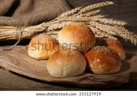 Tasty buns with sesame on wooden background - stock photo